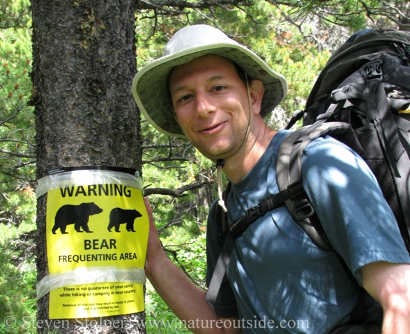 hiker beside bear warning sign Glacier National Park
