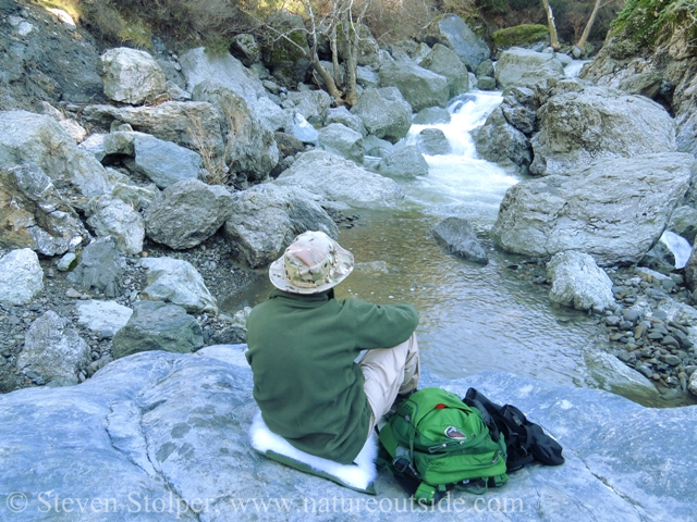 hiker sitting on rocks in front of waterfall