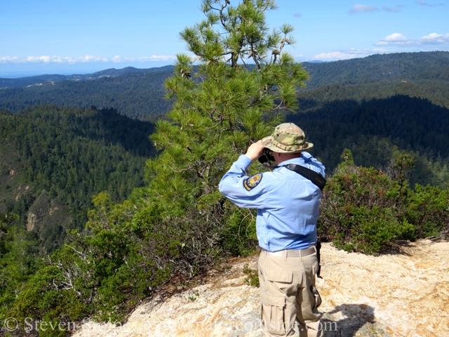 hiker on mountain top looking through Nikon Monarch 5 8x42 binoculars