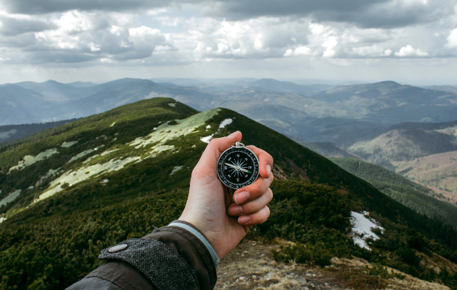 hand holding compass in mountains Photo by Anastasia Petrova, Unsplash